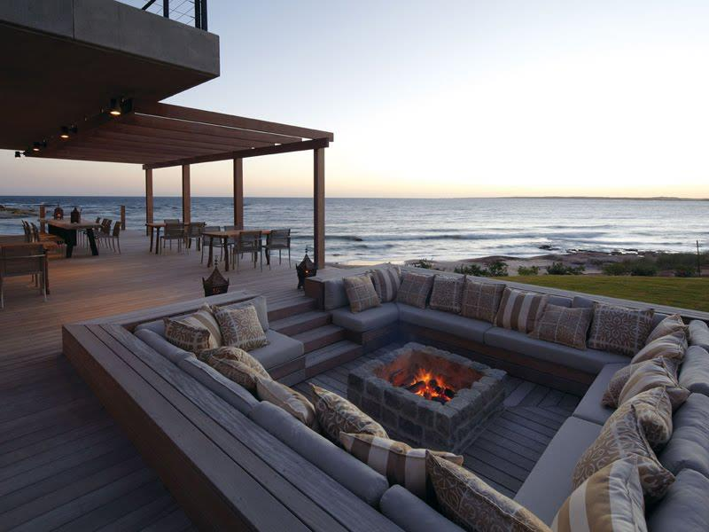Outdoor sitting area in front of the sea with fireplace on the table.